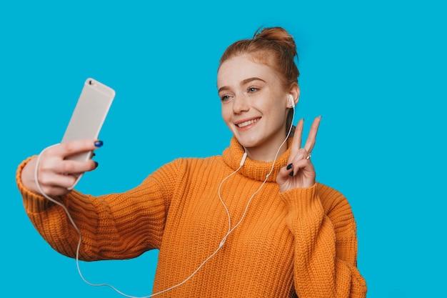 Portret van een mooie roodharige vrouw met sproeten doet een selfie met haar smartphone glimlachend vrede met vingers tonen tegen blauwe studio achtergrond.