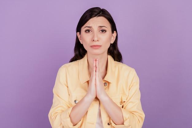 Portret van een mooie, schattige vrouw die haar handpalmen bij elkaar houdt en hulp vraagt op een violette achtergrond