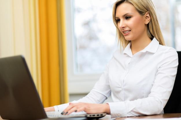 Portret van een mooie secretaressezitting bij haar bureau
