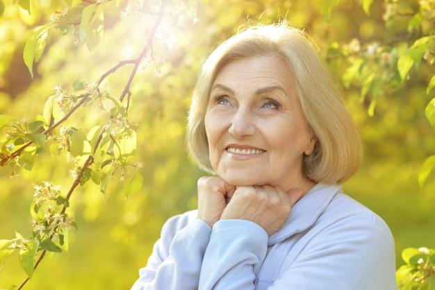 Portret van een mooie senior vrouw in groen park bij zonsondergang