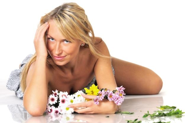 Portret van een mooie sexy jonge blonde vrouw poseren in studio in een mini-jurk met bloemen