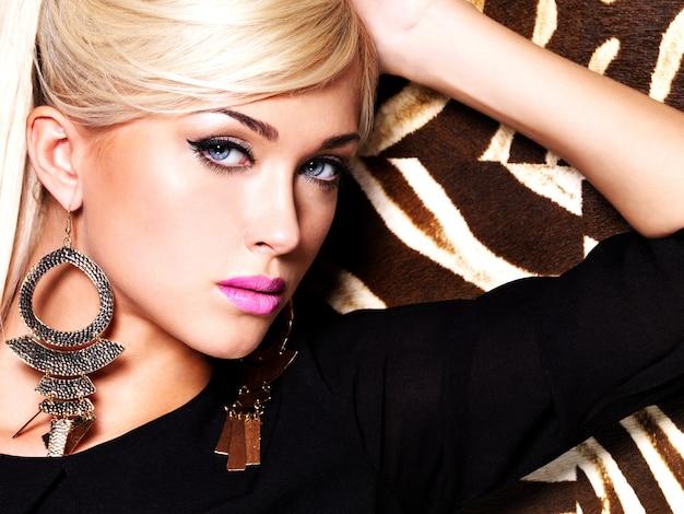 Portret van een mooie sexy vrouw met maniermake-up op gezicht en lange witte haren. glamour girl poseert over creatieve gestreepte ruimte