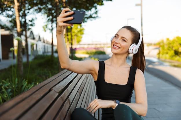 Portret van een mooie sportvrouw met een trainingspak in een koptelefoon die selfie neemt portret op een smartphone terwijl ze op een bankje in het stadspark zit