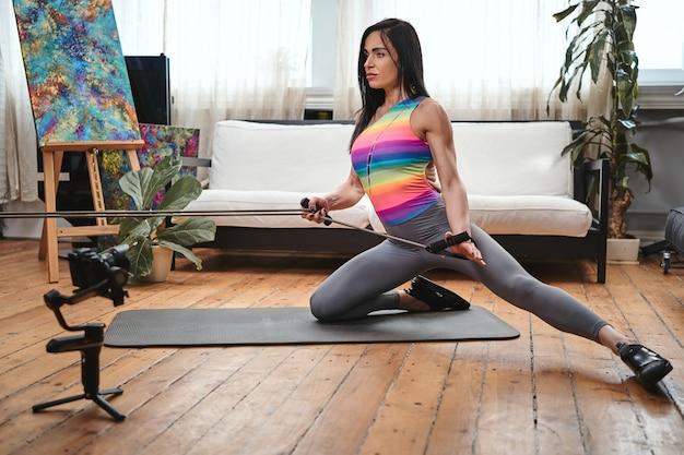 Portret van een mooie sportvrouw van middelbare leeftijd met zwarte haren en elastische banden die thuis wat oefeningen op mat doet.