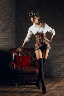 Portret van een mooie steampunk vrouw in lingerie en kousen, hoed en bril.