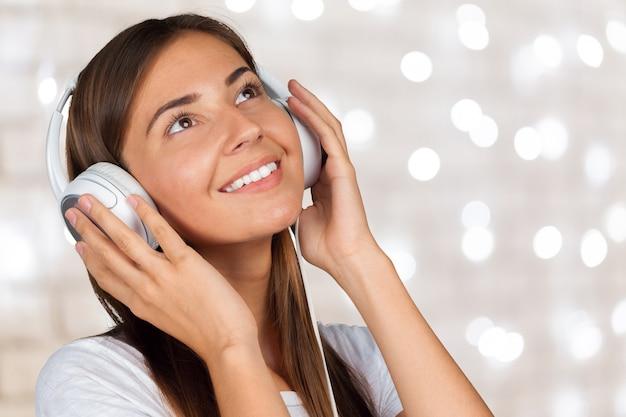 Portret van een mooie studente die aan muziek luistert