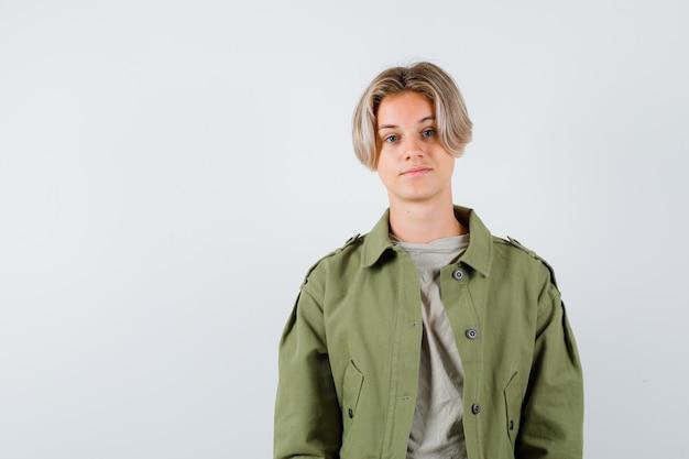 Portret van een mooie tienerjongen die naar de camera in een groen jasje kijkt en er slim vooraanzicht uitziet