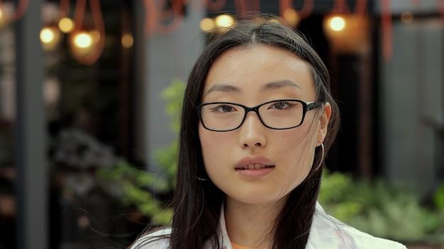Portret van een mooie trendy aziatische vrouw in een bril die naar de camera glimlacht en er aantrekkelijke portretten van mensen uitziet