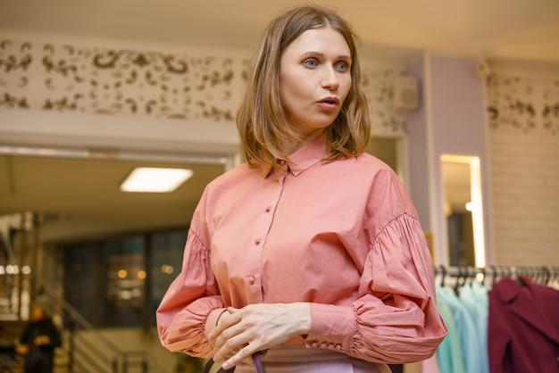 Portret van een mooie verraste vrouw in de winkel
