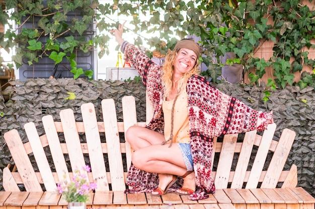 Portret van een mooie volwassen alternatieve hippieklerenvrouw in een vrolijke en gelukkige vrijetijdsbesteding in de buitenlucht