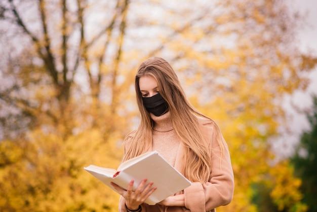 Portret van een mooie volwassen jonge vrouw op de achtergrond van de herfst in park in medische gezichtsmasker
