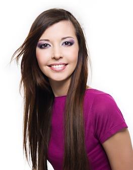Portret van een mooie vrolijke jonge vrouw met brede glimlach en lang bruin haar - dat op wit wordt geïsoleerd