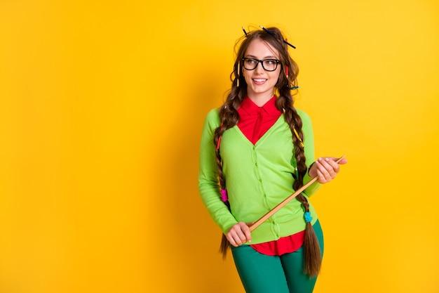 Portret van een mooie, vrolijke, slimme meid die de aanwijzer in handen houdt en lesgeeft over een levendige gele kleurachtergrond