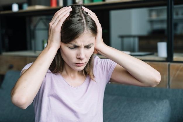 Portret van een mooie vrouw die aan hoofdpijn lijdt