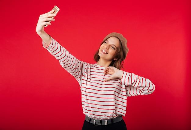 Portret van een mooie vrouw die baret draagt die een selfie neemt
