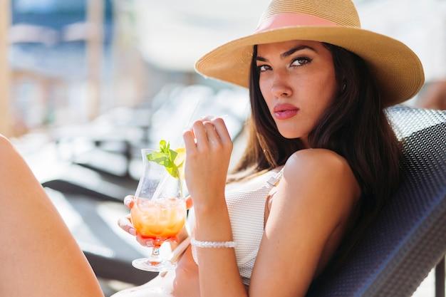 Portret van een mooie vrouw die cocktails drinkt tijdens het zonnebaden