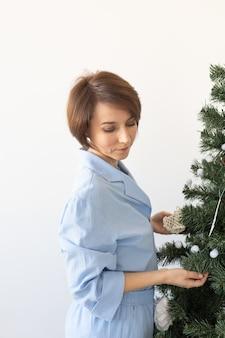 Portret van een mooie vrouw die de kerstboom versiert
