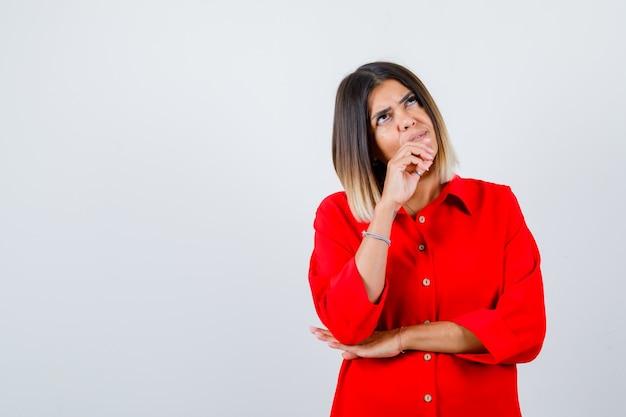 Portret van een mooie vrouw die de kin bij de hand houdt, omhoog kijkt in een rode blouse en peinzend vooraanzicht kijkt