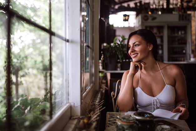 Portret van een mooie vrouw die door venster kijkt terwijl het zitten in serre of sunroom.