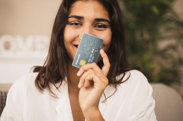 Portret van een mooie vrouw die een creditcard toont