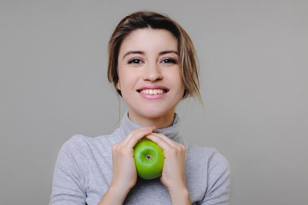 Portret van een mooie vrouw die een groene appel met beide handen houdt terwijl zij in camera kijkt die tegen een grijze achtergrond glimlacht. vrouw die in grijze kleren geïsoleerd glimlachen.