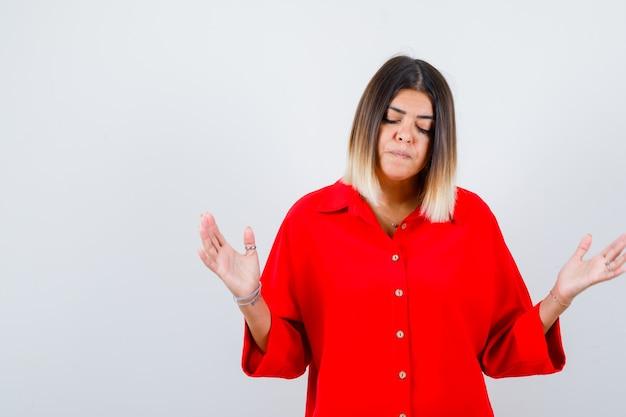 Portret van een mooie vrouw die een hulpeloos gebaar toont, naar beneden kijkt in een rode blouse en van streek kijkt