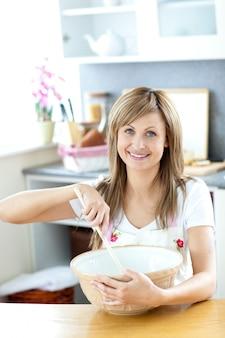 Portret van een mooie vrouw die een maaltijd in de keuken voorbereidt