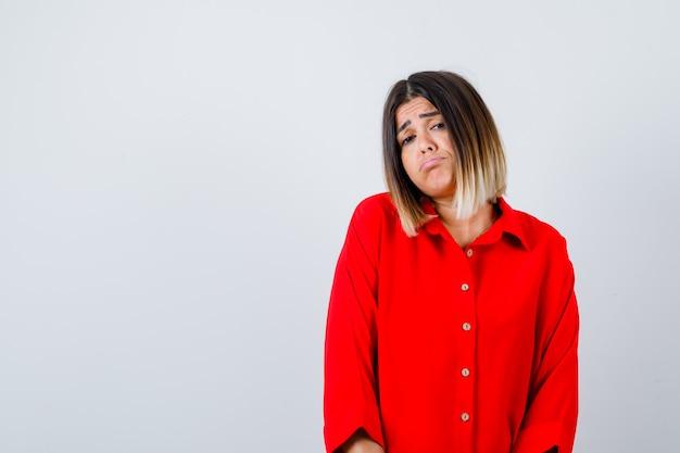 Portret van een mooie vrouw die een onderlip buigt in een rode blouse en er wanhopig vooraanzicht uitziet
