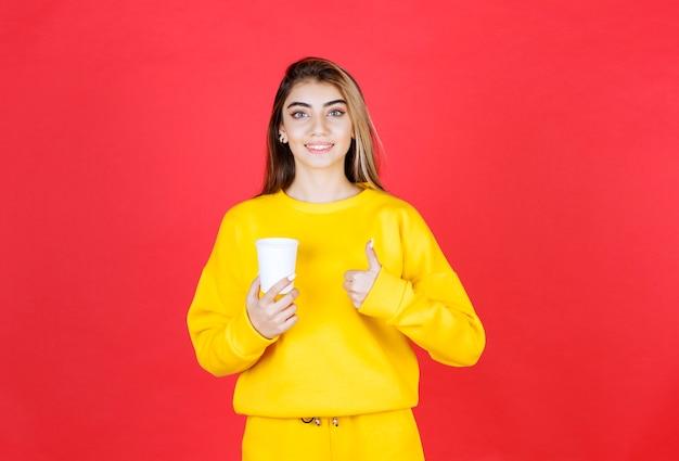 Portret van een mooie vrouw die een plastic kopje thee vasthoudt en duimen omhoog geeft