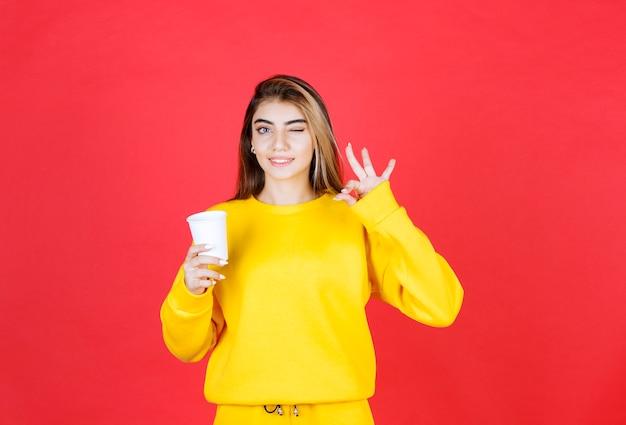 Portret van een mooie vrouw die een plastic kopje thee vasthoudt en een goed teken geeft