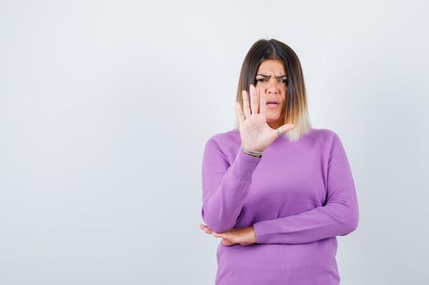 Portret van een mooie vrouw die een stopgebaar in een paarse trui toont en er serieus vooraanzicht uitziet