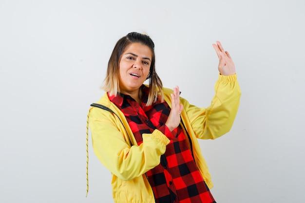 Portret van een mooie vrouw die een stopgebaar in shirt, jas toont en beschaamd vooraanzicht kijkt