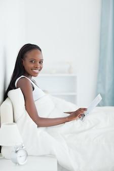 Portret van een mooie vrouw die een tabletcomputer met behulp van