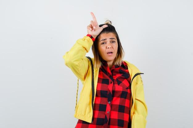 Portret van een mooie vrouw die een verliezer teken op het hoofd in shirt, jas laat zien en er teleurgesteld vooraanzicht uitziet