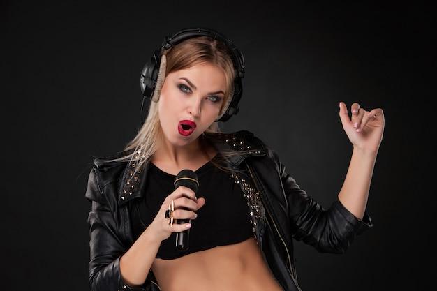 Portret van een mooie vrouw die in microfoon met hoofdtelefoons binnen zingen op zwarte muur