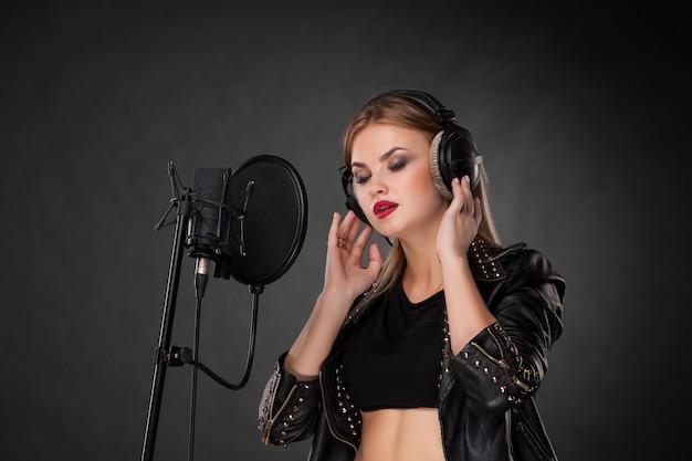 Portret van een mooie vrouw die in microfoon met hoofdtelefoons in studio op zwarte achtergrond zingt