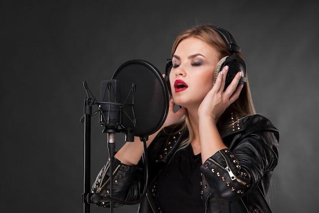 Portret van een mooie vrouw die in microfoon met hoofdtelefoons zingt