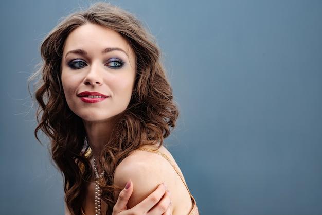 Portret van een mooie vrouw die koesteren door de schouders terug kijkend