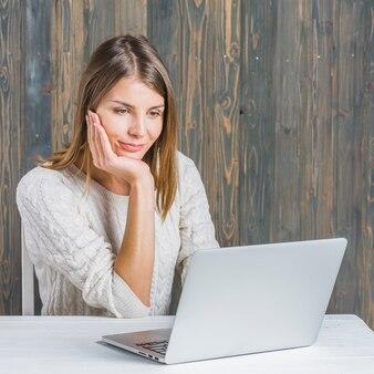 Portret van een mooie vrouw die laptop over bureau met behulp van