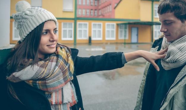 Portret van een mooie vrouw die met haar hand afwijst naar een jonge man na een ruzie buitenshuis. paar relaties en problemen concept.
