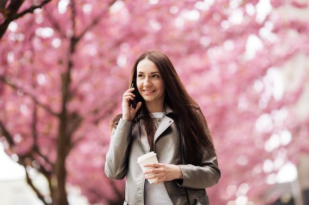 Portret van een mooie vrouw die met haar telefoon in sakura-boompark spreekt