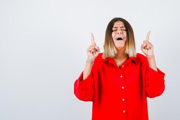 Portret van een mooie vrouw die naar boven wijst, de ogen gesloten houdt in een rode blouse en er een gelukzalig vooraanzicht uitziet