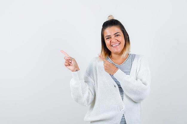 Portret van een mooie vrouw die naar de linkerbovenhoek wijst in t-shirt, vest en er vrolijk uitziet