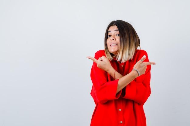 Portret van een mooie vrouw die naar rechts en links wijst in een rode blouse en besluiteloos vooraanzicht kijkt