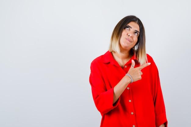 Portret van een mooie vrouw die naar rechts wijst, omhoog kijkt in een rode blouse en doordacht vooraanzicht kijkt