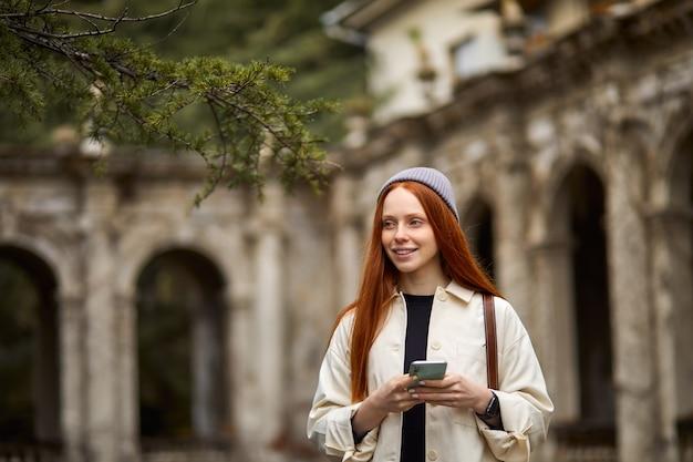 Portret van een mooie vrouw die naast een oud gebouw staat met behulp van touchscreen-technologie op smartphone-br...