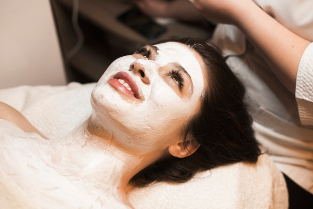 Portret van een mooie vrouw die op een kuuroordbed leunt met een wit masker op haar gezicht in een kuuroordcentrum.