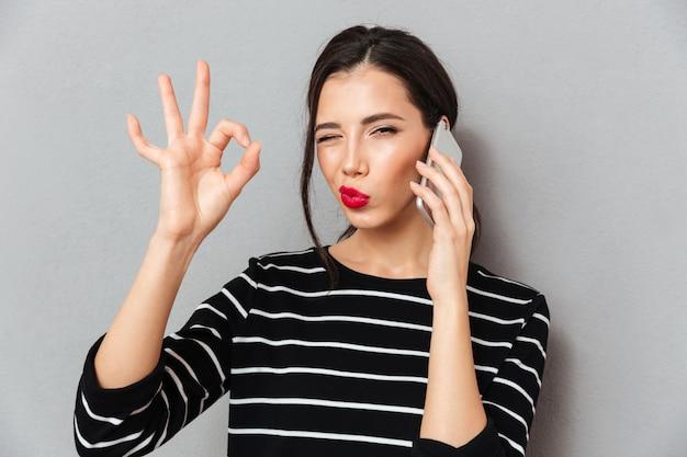 Portret van een mooie vrouw die op mobiele telefoon spreekt
