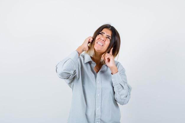 Portret van een mooie vrouw die oren stopt met vingers, omhoog kijkt in shirt en bang vooraanzicht kijkt