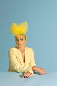Portret van een mooie vrouw die poseert met een avantgarde hoofddeksel